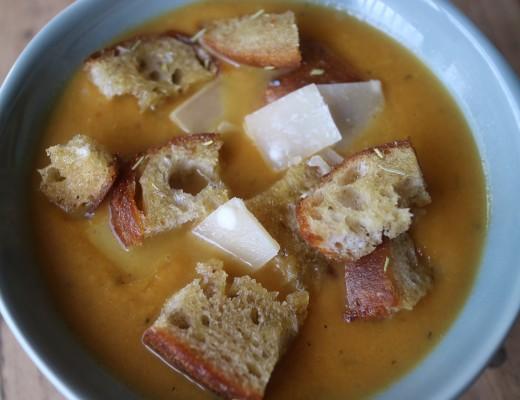 Pompoensoep, geroosterde pompoen, peen, ui, knoflook, rozemarijn, tijm uit de oven met knoflook rozemarijn croutons en Parmezaanse kaas